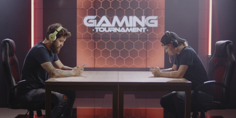 Medium shot of a man and woman competing at a mobile gaming tournament